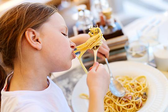 Kind isst Spaghettis